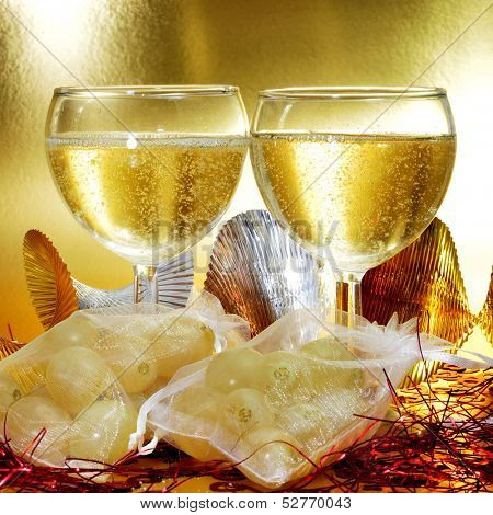 some glasses with spanish champagne and sachets with the twelve grapes of luck, traditional on the New Year