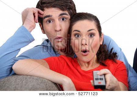 Shocked couple watching television