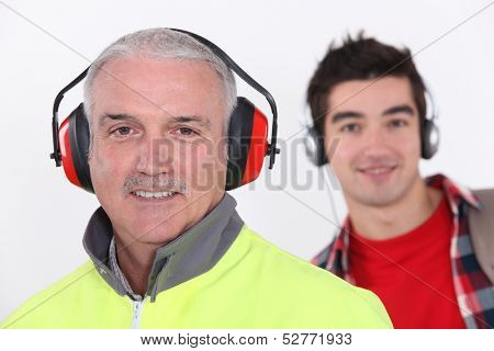 Builder with earmuff stood in front of teenager with headphones