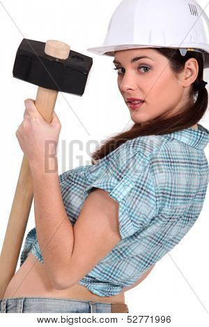 sexy craftswoman holding a huge hammer