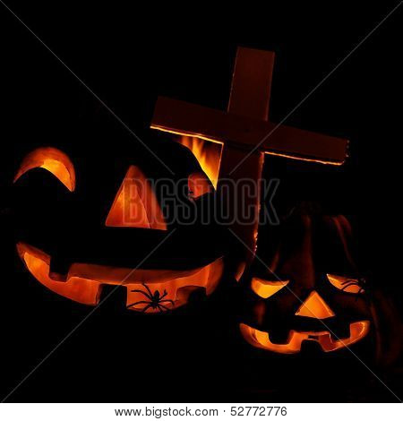 Scary glowing pumpkin decoration with creepy spider, burning fire, cross on the cemetery, Halloween fun, misterious holiday celebration
