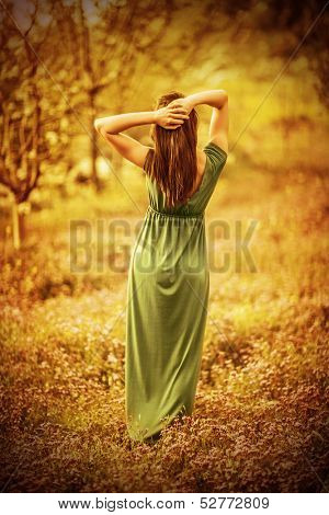 Sensual nymph in autumn garden, back side of sexy girl wearing long dress, enjoying autumnal nature in the park, fairy-tale concept