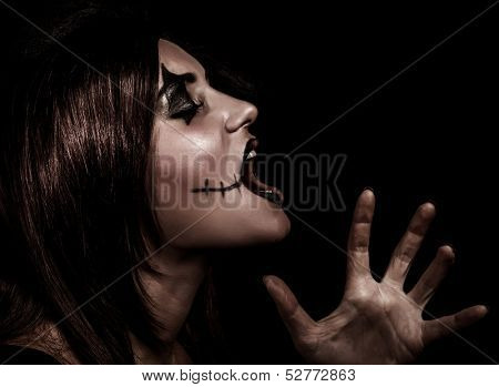 Scary witch yelling, side view of aggresive woman with painted face on black background, terrible grimace, Halloween party concept