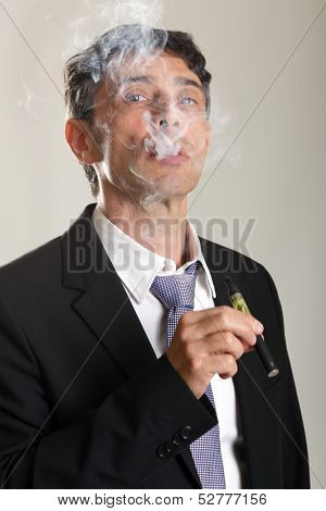 Middle aged confident man enjoying smoking an e-cigarette or vaporizer exhaling a cloud of smoke and peering through the fumes with a look of satisfaction