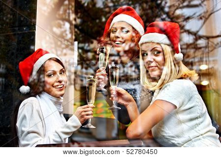 Women in santa hat drinking champagne in cafeteria.