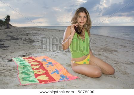 Attractive Lady Sitting On A Towel Holding Sunglasses