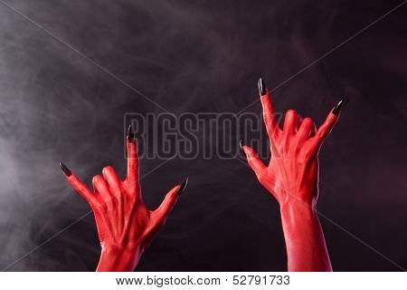 Red devil hands showing heavy metal gesture, studio shot on smoky background