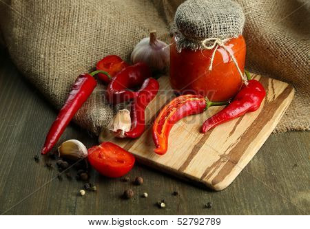 Composition with salsa sauce in glass jar,, red hot chili peppers  and garlic, on sackcloth,  on wooden background