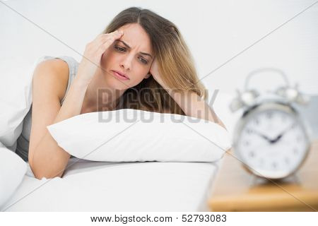 Suffering young woman having headache lying on her bed in the bedroom