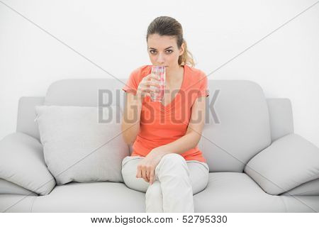 Attractive casual woman drinking a glass of water looking at camera sitting on a sofa