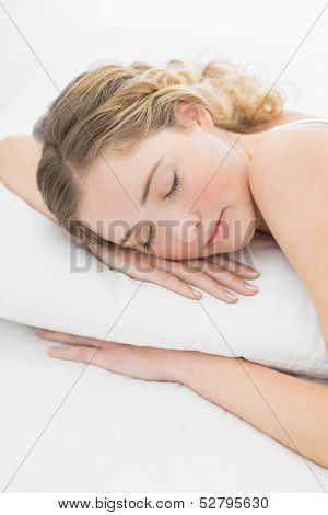 Pretty peaceful blonde lying in bed slumbering in bright bedroom