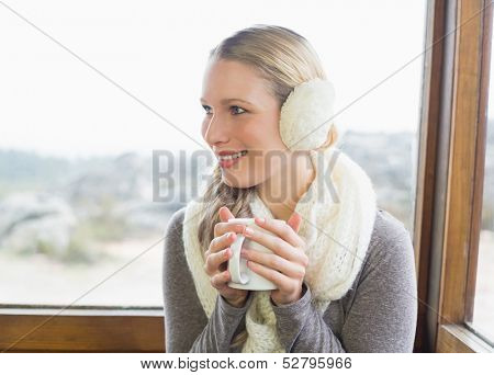Close-up of a smiling young woman wearing earmuff with coffee cup against cabin window
