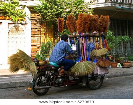 Street vendor selling brooms from his bicycle