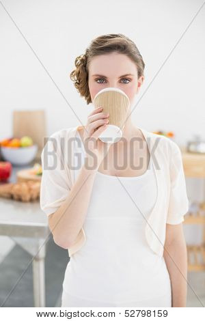 Cute woman standing in kitchen drinking of disposable cup looking at camera