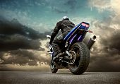 stock photo of motorcycle  - Man seat on the motorcycle under sky with clouds - JPG
