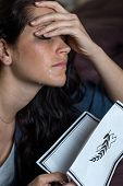 picture of obituary  - Portrait of crying young woman holding obituary - JPG