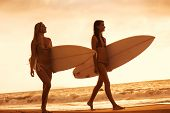 Beautiful Surfer Girls Walking on the Beach at Sunset in Hawaii