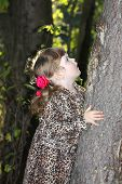 stock photo of overcoats  - Pretty little girl with pink bows in overcoat keeps tree and looks up in forest.