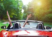 pic of speeding car  - Happy beautiful blond young woman driving a sports car - JPG