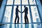 stock photo of striking  - Silhouettes of two successful businessmen handshaking after striking deal - JPG