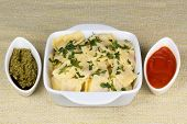 Italian pasta ravioli with parsley pesto sauce and tomato sauce