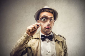stock photo of investigation  - investigator looking with magnifying glass - JPG