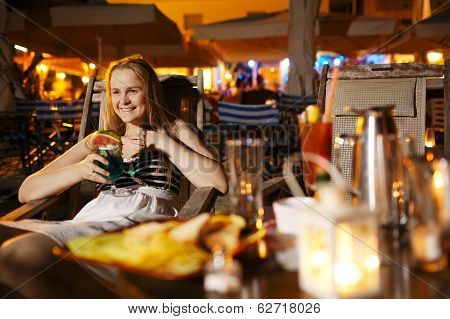 Smiling woman drinking in a cafeteria
