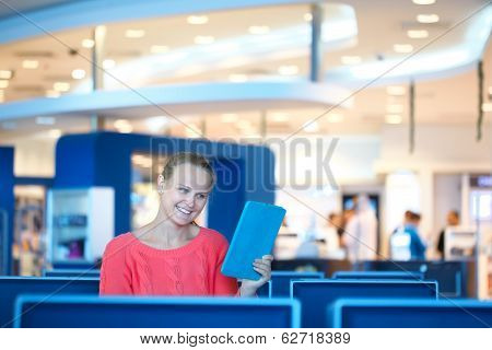 Woman sitting in a waiting room reading tablet