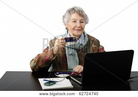 Smiling Old Lady Drinking Cup Of Coffee While Talking In Skype