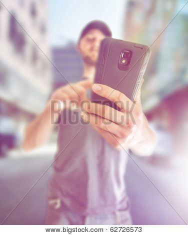 a young man using a cell phone to send a text message or make a phone call or browse the internet, done with a creative filter