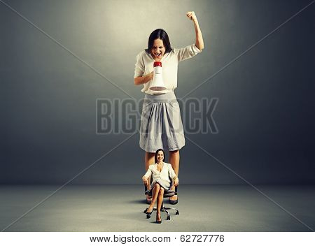 angry woman and smiley calm woman on the chair over dark background