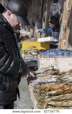 Irkutsk region, Russia-March,23 2014:Man chooses cisco in the fish market in Listvyanka, Lake Baikal