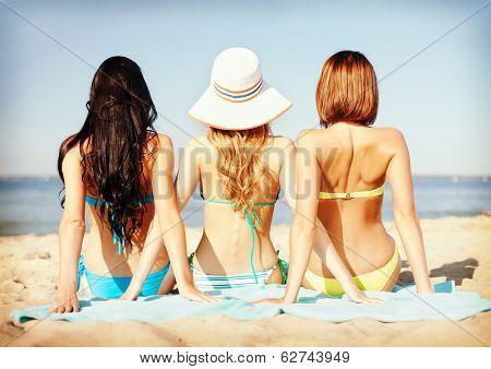 summer holidays and vacation - girls sunbathing on the beach