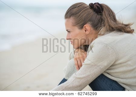 Calm Young Woman Sitting On Cold Beach And Looking Into Distance
