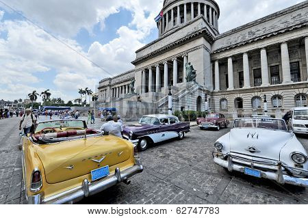 Old American cars parked in front of El Capitolio
