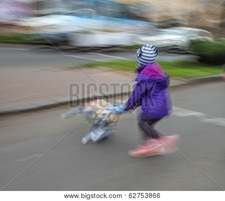 Little Girl With Toy Stroller Crossing The Road
