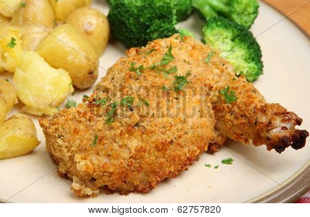 Chicken Kiev breast with broccoli and new potatoes.