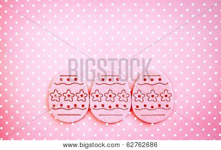 Decorated felt easter eggs pink on a pinky polka dots background