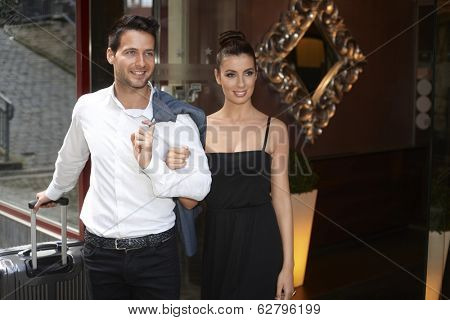 Attractive couple standing in hotel doorway with suitcase, waiting for transfer.
