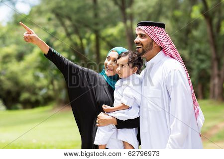 cute arabian family looking and pointing in the forest