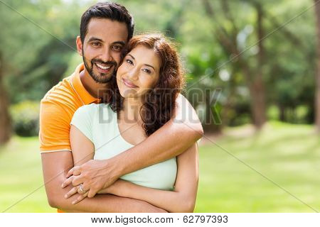 lovely young indian couple hugging outdoors