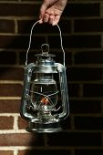 image of kerosene lamp  - Hand holding kerosene lamp on brick wall background - JPG