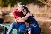 pic of biracial  - Young Caucasian man hugging his biracial girlfriend sitting together on dock over lake - JPG