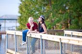 Young Interracial Couple Standing Together On Wooden Pier Overlooking Lake
