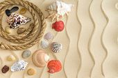 picture of coiled  - Marine still life with a collection of different seashells waterworn pebbles and stones and a coiled rope on golden beach sand decorated with ridged wavy lines - JPG
