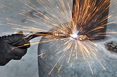 stock photo of welding  - Arc welding of a steel welder hands in gloves tool and sparks - JPG