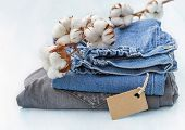 stock photo of boll  - Stack of clothes with a sprig of cotton - JPG