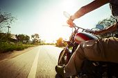 stock photo of chopper  - Biker riding motorcycle  on an empty road at sunny day - JPG