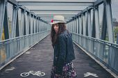 picture of girl walking away  - Pretty girl with long hair walking away on a bridge