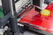 picture of abs  - Detail of a 3D printer printing with a yellow ABS filament  - JPG